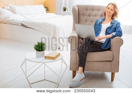 Feeling Good. Calm Peaceful Young Woman Sitting In A Comfortable Armchair With Her Eyes Closed And F