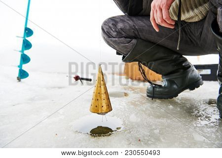 fishing at winter. Fisherman feeding and luring fish with feeder