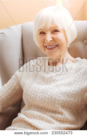 Baby Boomer. Cute Pretty Senior Woman Smiling And Feeling Happy While Sitting In A Soft Comfortable