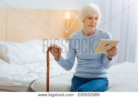 Aged Woman. Calm Serious Tired Aged Woman With A Wooden Walking Stick Sitting On Big Soft Bed And Th