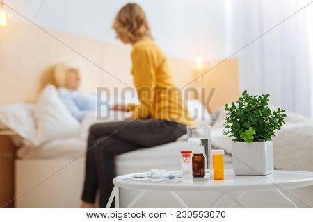 Illness. Tired Aged Ill Woman Staying In Bed With Her Caring Attentive Young Granddaughter Sitting B