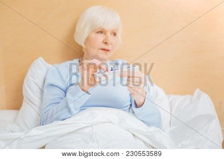 Convenient Pillbox. Tired Ill Senior Woman Feeling Unwell And Holding A Convenient Pillbox While Bei