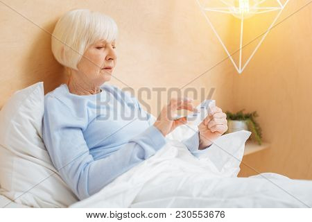 Taking Pills. Smart Responsible Ill Aged Woman Staying In Her Comfortable Soft Bed And Looking At Th