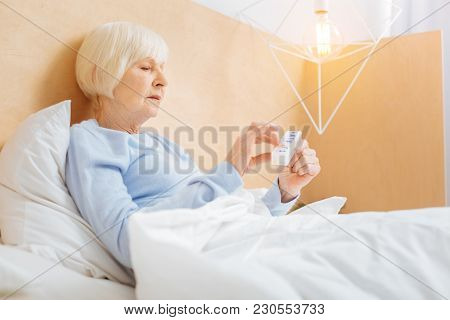 Necessary Pills. Serious Thoughtful Ill Aged Woman Looking Concentrated While Staying In Bed And Tak