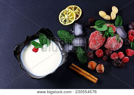 Frozen Raspberry, Berry, Strawberries, Yoghurt Plate Mint Leaves, Pieces Of Ice On A Black Shale Boa