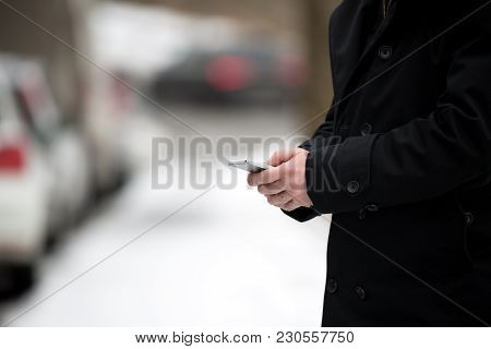 Businessman Holding A Smartphone Mobile, Stuck In Traffic On A Snowy Cold Winter Day. Man In Coat Te