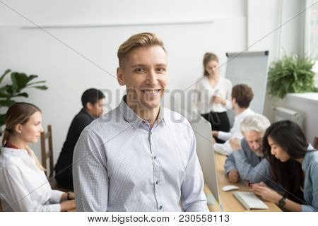 Smiling Young Businessman Looking At Camera With Diverse Team Office People Employees At Background,