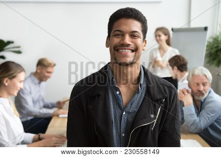 Smiling African American Office Employee Or Leader Looking At Camera With Diverse Colleagues At Back