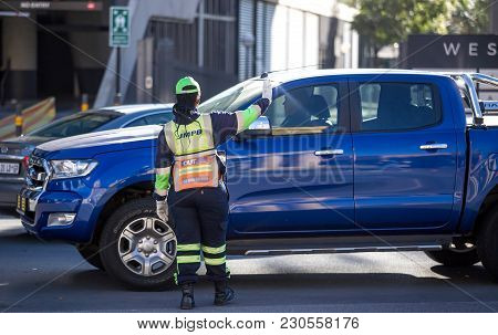 Johannesburg, South Africa - March 8, 2018: Traffic Officer Holding Hand Up To Traffic With Car In B