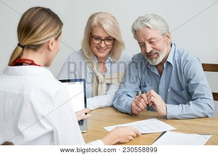 Real Estate Agent Showing House Plan To Aged Couple, Realtor Making Property For Sale Offer To Senio