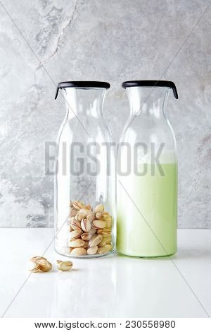 Fresh Homemade Pistachio Milk In A Transparent Bottle And Pistachio Nuts. Vegetarian Alternative To