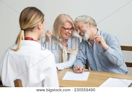 Loving Caring Senior Aged Couple Laughing Signing Documents At Meeting With Financial Advisor, Happy