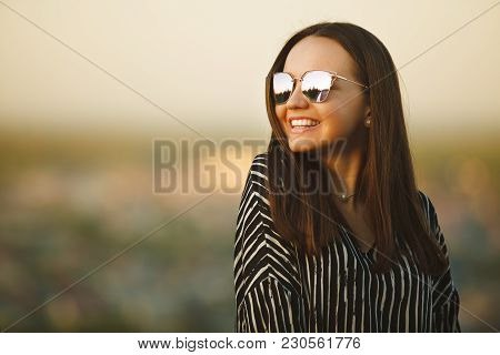 Portrait Of A Young Smiling Girl In Sunglasses With Reflective Glasses. Nice Woman With Natural Hair