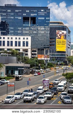 Johannesburg, South Africa - March 8, 2018: Traffic Waiting At Intersection With Buildings In Backgr