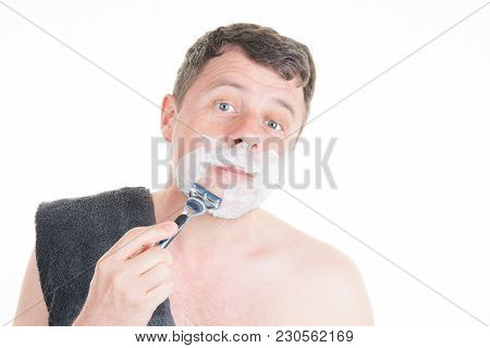 Handsome Man Shaves With A Hand Razor And Shaving Foam In The Bathroom