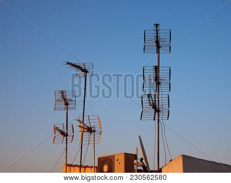 Tall Metal Antennas On Roof With Blue Sky At Dusk