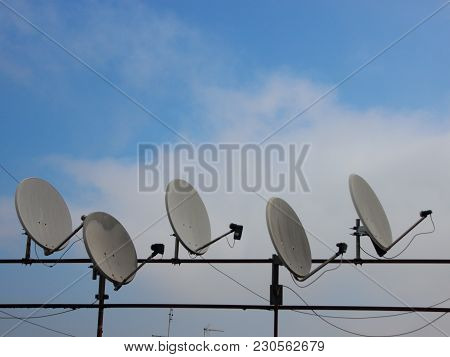 Satellite Dish On Metal Railing With Sky Background