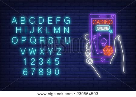 Casino Online Neon Sign. English Alphabet And Numbers. Hand Holding Smartphone With Dice And Playing