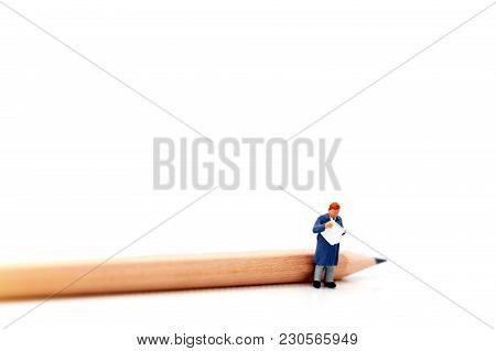 Miniature People: Businessman Standing With Pencil And Book. Concept Of Education And Business.
