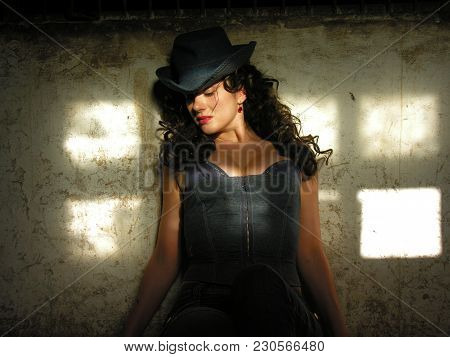 Attractive  Cowgirl Sitting  In The Old Stable Without Horse