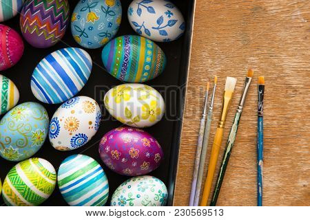 Easter eggs and brushes on wooden background