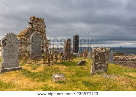 Laide, Scotland - June 8, 2012: Chapel Wall Ruin At Laide Historic Beach Side Cemetery Under Gray-bl
