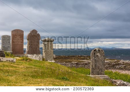 Laide, Scotland - June 8, 2012: Tombstones At Laide Historic Beach Side Cemetery Under Dark Gray Hea