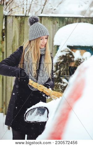 Winter Portrait Of A Young Woman Cleaning Snow From A Car. Beauty Blonde Model Girl Laughs And Cheer
