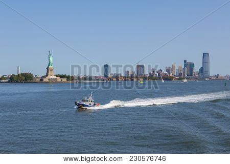 Nypd Boat Patrolling East River. In The Background Statue Of Liberty And Skyscrapers New Jersey.