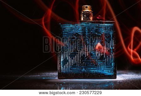 Glass Of Perfume On A Dark Background In Flames