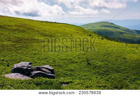 Grassy Meadow With Peak In A Distance. Huge Rock On Hillside. Lovely Summer Landscape In Mountains