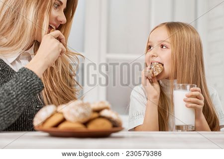Photo Of Mother And Daughter Eating Cookies And Smile.