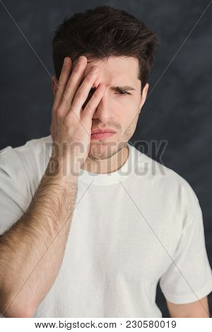 Young Stressed Man Cover His Face With Hand. Exhausted Depressed Guy Portrait, Gray Studio Backgroun