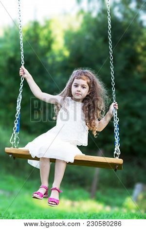 Beautiful Little Girl Sitting On Swing At Summer Day, Happy Childhood Concept