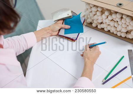 Workplace Interior Designer. Interior Designer Draws At Desk In Office With Pencil.