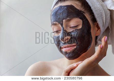 Beauty Portrait Of A Smiling Brunette Woman In A Towel On The Head Applying Black Nourishing Mask On