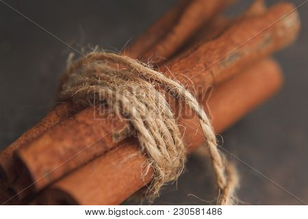 Some Cinnamon Sticks In Bundle Tied With Jute Twine On Dark Background. Selective Focus