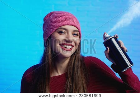 Smiling Pretty Female With Long Hair Wearing Red Hat And Sweater Posing With Paint Spray In Her Hand