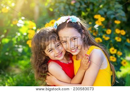 Two Cute Little Girls Embracing And Smiling At The Sunny Countryside. Happy Kids Outdoors