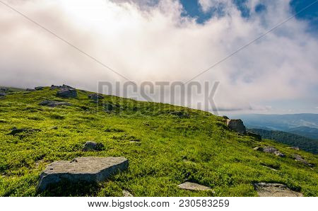 Grassy Meadow With Boulders Under The Huge Cloud. Beautiful Landscape On Fresh Summer Morning