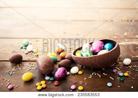 Chocolate Easter Eggs And Sweet Candies On Wooden  Background. Happy Easter!