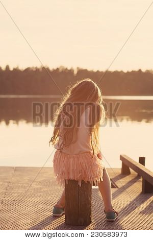 Sad Beautiful Teen Girl Is Sitting  At Seaside During Sunset.  Back View