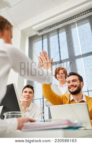 Colleagues celebrate success with High Five as business team