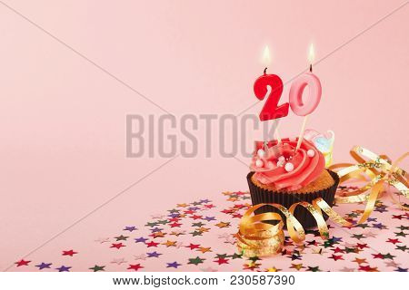20th Birthday Cupcake With Candles, Sprinkles And Ribbon On Pink Background. Card Mockup, Copy Space