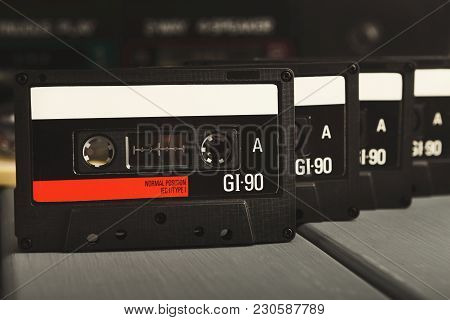 Row Of Retro Audio Cassettes In Front Of Vintage Tape Recorder On Gray Background. Side View On Old-