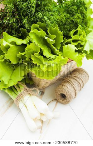Fresh Green Lettuce Salad With Parsley, Rosemary, Onion In Basket On A Wooden Background
