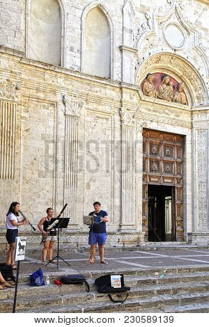 Montepulciano, Italy - July 19, 2017: Street Musicians On Steps Of Cathedral In Medieval Tuscan Town