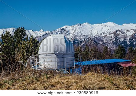 Small Astronomical Observatory With Telescope In Caucasian Mountains With Snow Peaks