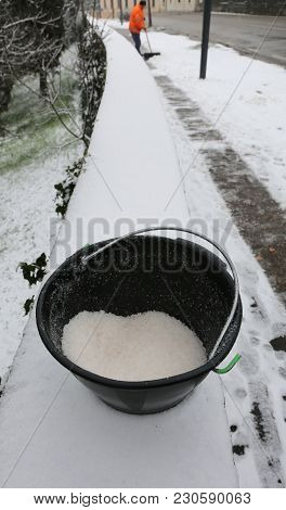 Bucket With Salt To Avoid The Falls On The Ice Of The Sidewalk And The Maintenance Worker Of The Roa