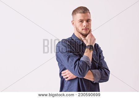 Portrait of young thoughtful man holding hand on chin and looking to camera while isolated over white background. Stylish handsome bearded hipster in denim shirt. Pensive male isolated
